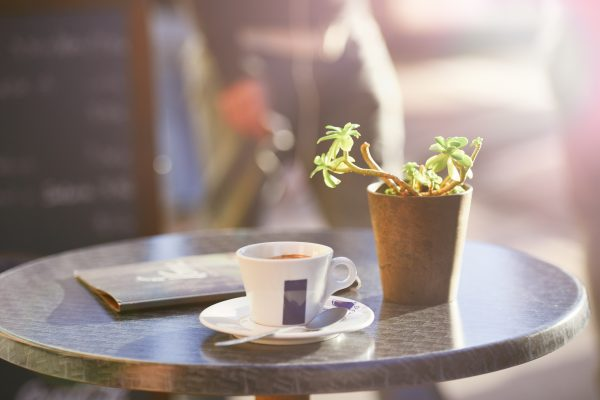 Morning Coffee On Outside Cafe Table With Plant & Menu