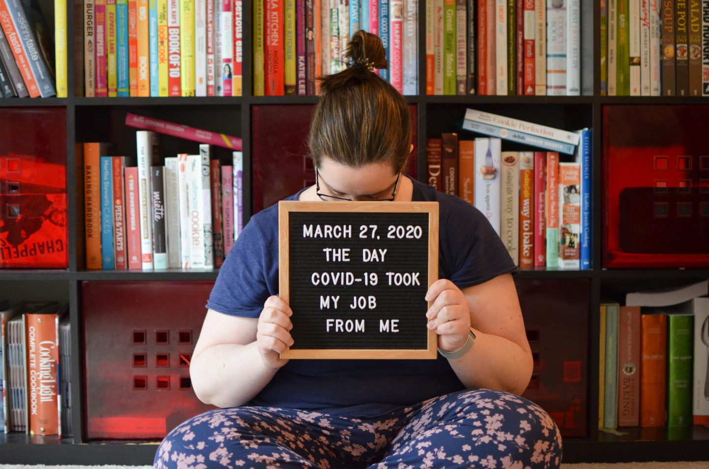 Photo of a woman with a letterboard sign displaying the date she was laid off because of COVID-19